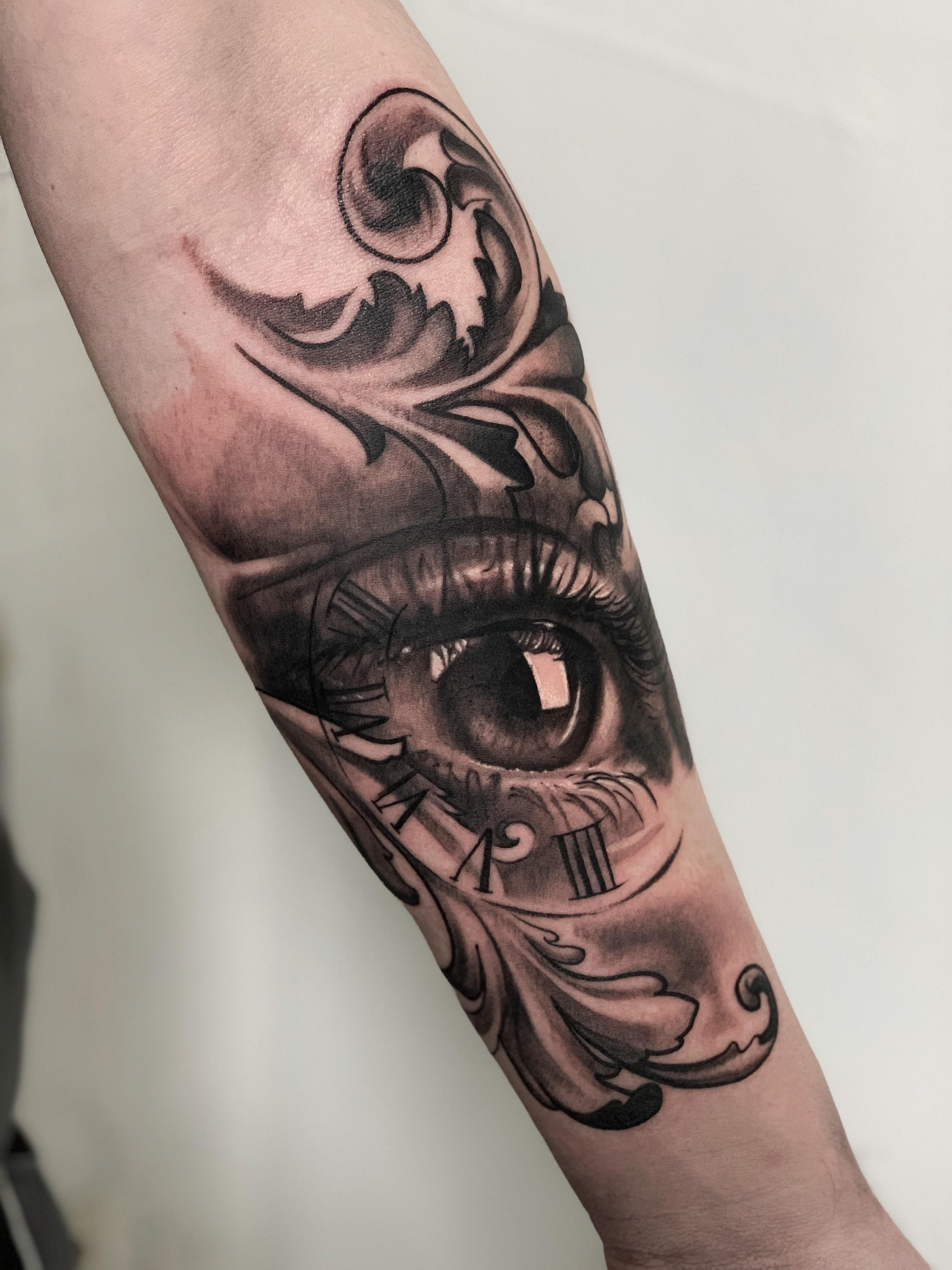 realistic eye tattoo with clock and ornamental designs done in kitzingen