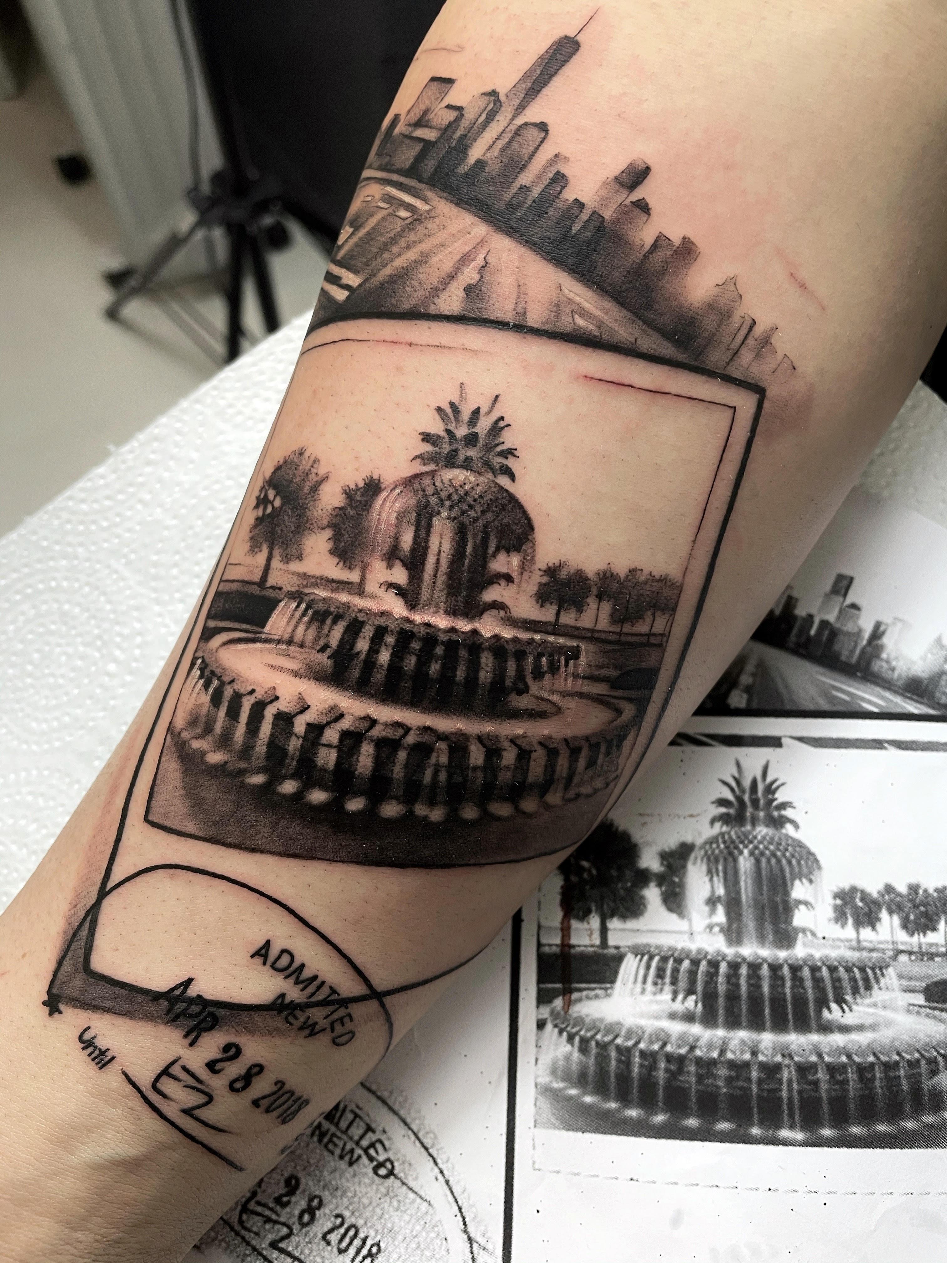 polaroid tattoo of a fountain and city